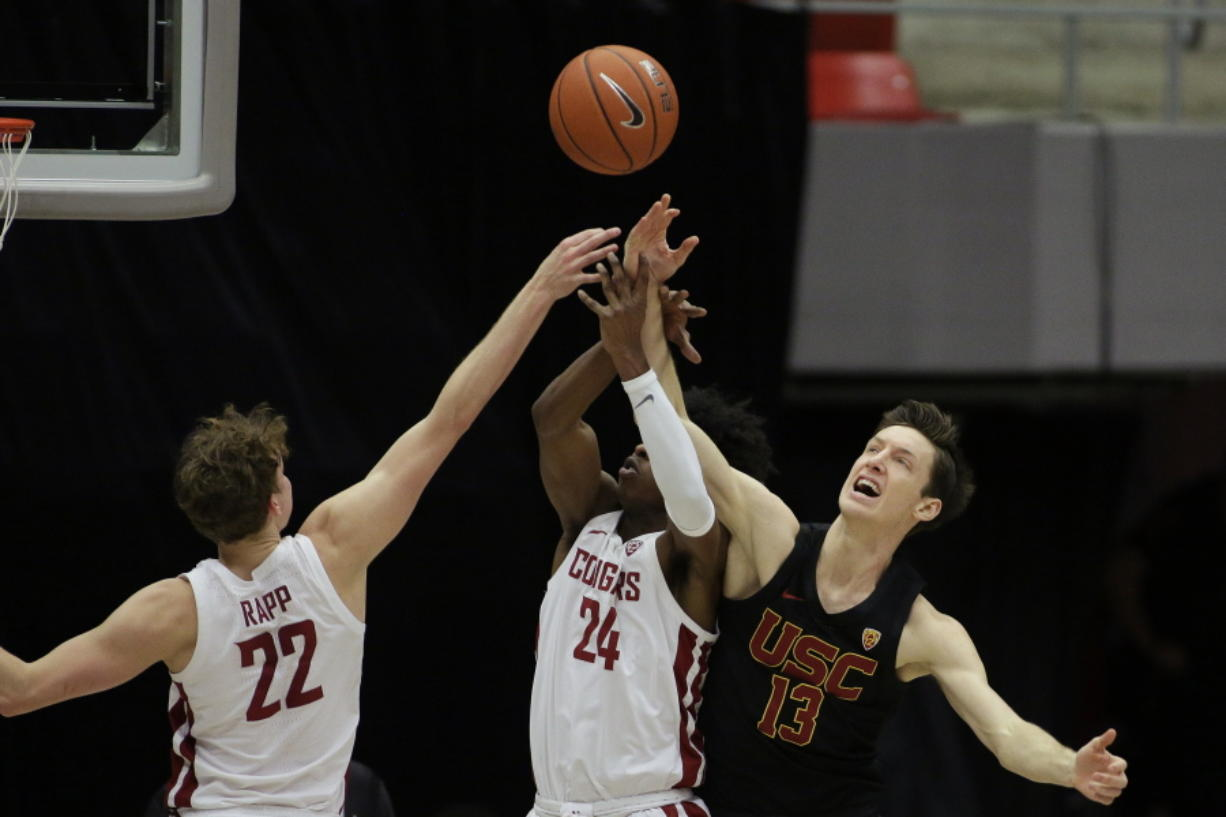 Washington State guards Ryan Rapp (22) and Noah Williams (24) and Southern California guard Drew Peterson (13) go after a rebound during the second half of an NCAA college basketball game in Pullman, Wash., Saturday, Feb. 13, 2021.