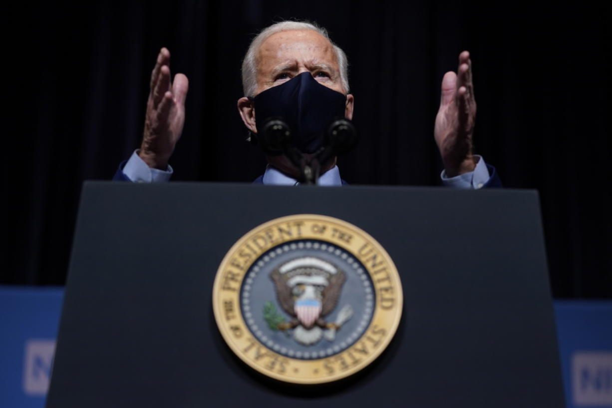 FILE - In this Feb. 11, 2021, file photo, President Joe Biden speaks during a visit to the Viral Pathogenesis Laboratory at the National Institutes of Health in Bethesda, Md. A federal judge late Tuesday, Feb. 23, 2021,  indefinitely banned President Joe Biden's administration from enforcing a 100-day moratorium on most deportations.