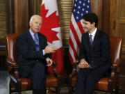 FILE - In this Dec. 9, 2016 file photo, Canadian Prime Minister Justin Trudeau meets with then U.S. Vice President Joe Biden on Parliament Hill in Ottawa. Biden will still host Canadian Prime Minister Justin Trudeau on Tuesday for the first bilateral meeting but will do it virtually.