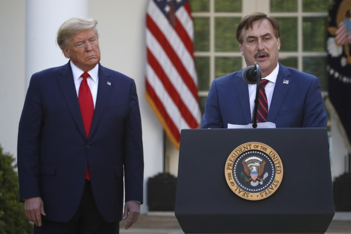 FILE - In this March 30, 2020, file photo, My Pillow CEO Mike Lindell speaks as President Donald Trump listens during a briefing about the coronavirus in the Rose Garden of the White House, in Washington. Twitter has permanently banned Lindell's Twitter account after he continually perpetuated the baseless claim that Donald Trump won the 2020 U.S. presidential election.