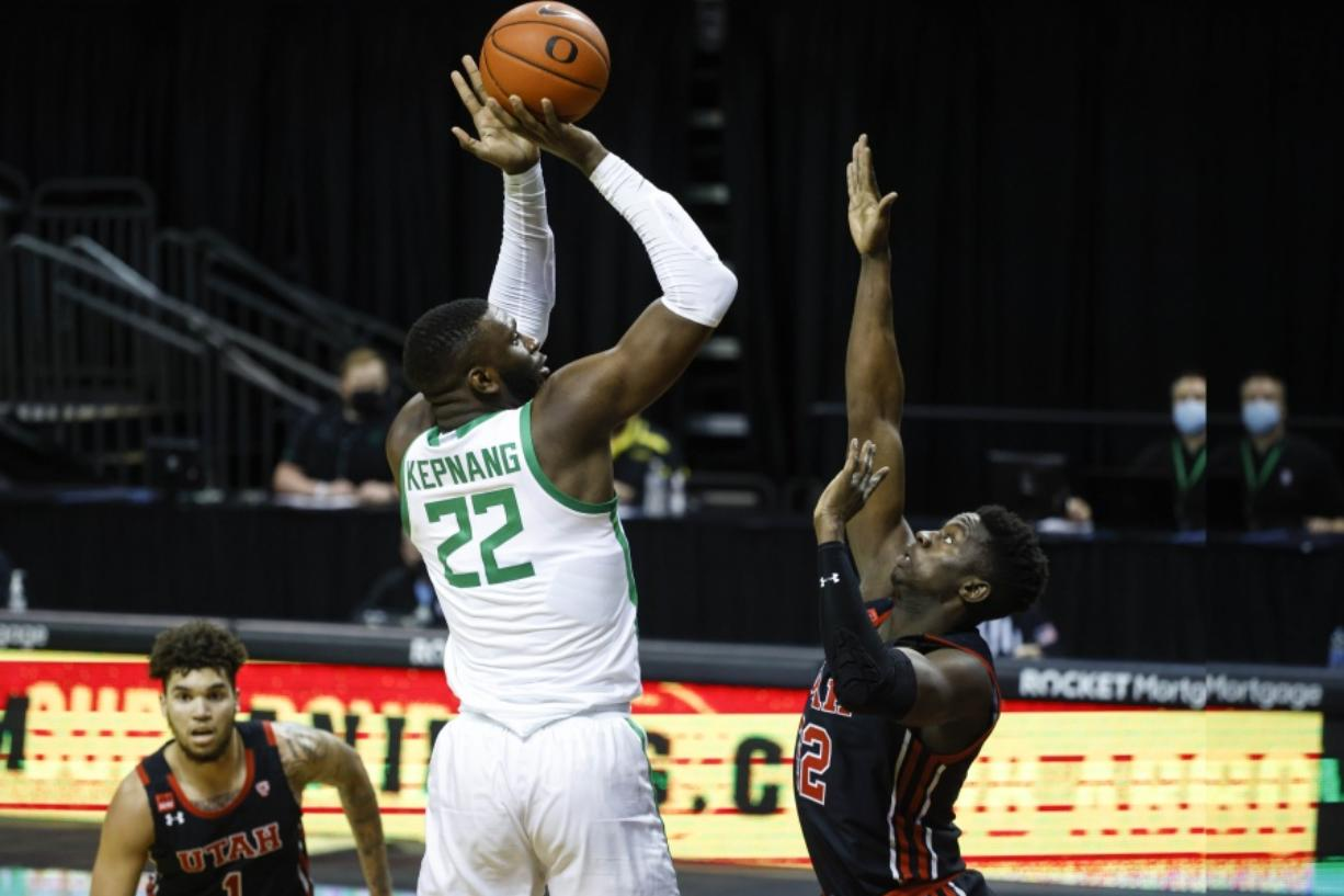 Oregon center Franck Kepnang (22) shoots over Utah center Lahat Thioune (32) during an NCAA college basketball game in Eugene, Ore., Saturday, Feb. 20, 2021.