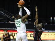 Oregon center Franck Kepnang (22) shoots over Utah center Lahat Thioune (32) during an NCAA college basketball game in Eugene, Ore., Saturday, Feb. 20, 2021.