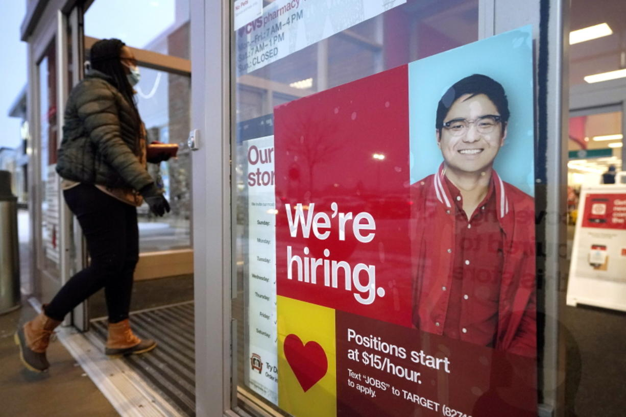 FILE - In this Feb. 9, 2021 file photo, a passer-by walks past an employment hiring sign while entering a Target store location, in Westwood, Mass.   The Federal Reserve says there's evidence that hiring has picked up in recent weeks, though the job market remains badly damaged by the pandemic. In its semi-annual monetary policy report released Friday, Feb. 19, the Fed says job data compiled by payroll processor ADP indicate that employment improved modestly through early February.