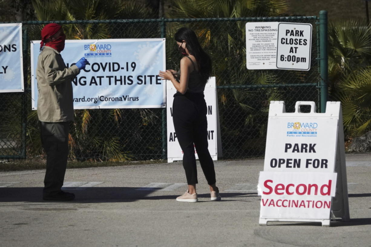 FILE - In this Jan. 27, 2021, file photo, woman asks directions at the entrance to Vista View Park where a COVID-19 vaccination site has opened for second doses in Davie, Fla. As health officials race to vaccinate people across the U.S., the need to give each person two doses a few weeks apart is adding a layer of complexity to the country's biggest-ever vaccination campaign.
