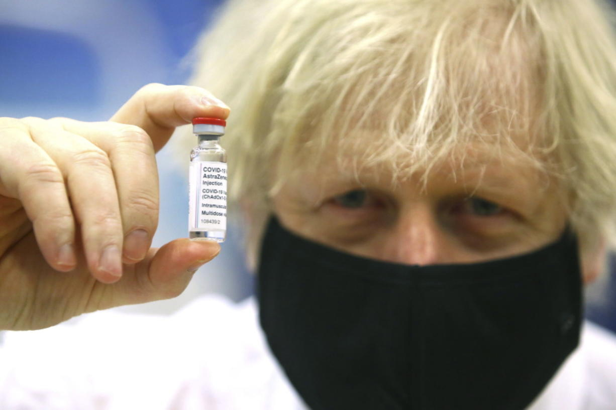 FILE - In this Wednesday, Feb. 17, 2021 file photo, Britain's Prime Minister Boris Johnson holds a vial of the Oxford/Astra Zeneca Covid-19 vaccine at a vaccination centre in Cwmbran, south Wales. The British government says it aims to give every adult in the country a first dose of coronavirus vaccine by July 31, a month earlier than its previous target. In addition, the goal is for everyone over 50 or with an underlying health condition to get a shot by April 15, rather than the previous target of May 1.