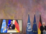 German President Frank-Walter Steinmeier, right, and Director General of the World Health Organization Tedros Adhanom Ghebreyesus, left on the screen, brief the media on a virtual joint news conference at Bellevue Palace in Berlin, Germany, Monday, Feb. 22, 2021.