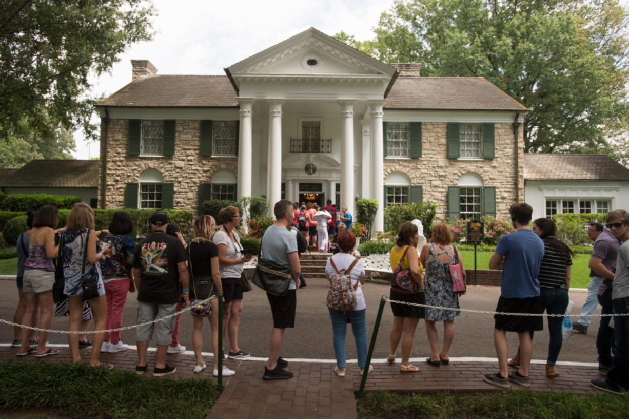FILE - In an Aug. 15, 2017 file photo, fans wait in line outside Graceland, Elvis Presley's Memphis home, in Memphis, Tenn. Elvis Presley's Graceland says it will reopen Thursday, May 21, 2020 after it shut down tours and exhibits due to the new coronavirus outbreak. The tourist attraction in Memphis, Tennessee, said Sunday that it has adjusted its tours, and restaurant and retail operations, since it closed in March.
