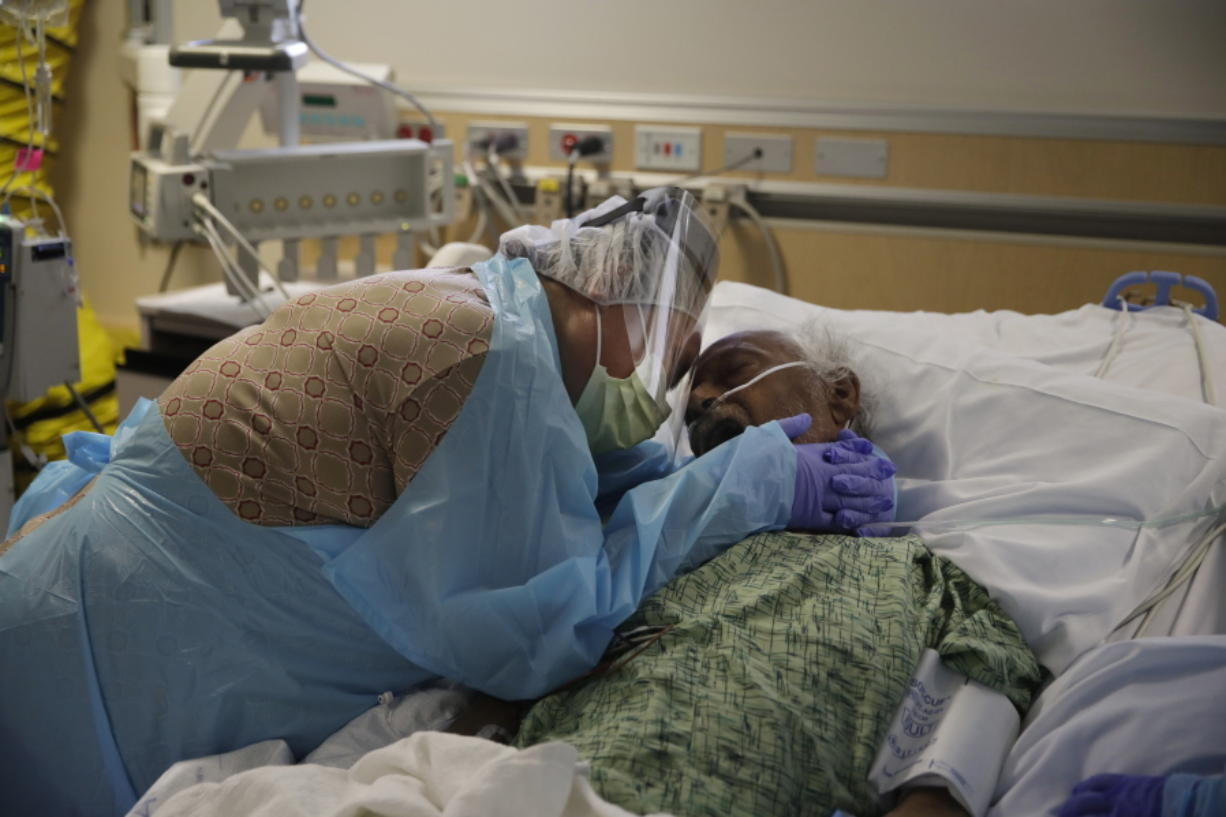 FILE - In this July 31, 2020, file photo, Romelia Navarro, 64, weeps while hugging her husband, Antonio, in his final moments in a COVID-19 unit at St. Jude Medical Center in Fullerton, Calif. The U.S. death toll from COVID-19 has almost topped 500,000 -- a number so staggering that a top health researchers says it is hard to imagine an American who hasn't lost a relative or doesn't know someone who died. (AP Photo/Jae C.