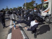 File - In this Sunday, Jan. 24, 2021 file photo, Israeli police officers clash with ultra-Orthodox Jews in Ashdod, Israel,. Ultra-Orthodox demonstrators clashed with Israeli police officers dispatched to close schools in Jerusalem and Ashdod that had opened in violation of coronavirus lockdown rules, on Sunday.