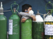 A youth rests on his empty oxygen cylinder waiting for a refill shop to open in the San Juan de Lurigancho neighborhood of Lima, Peru, Monday, Feb. 22, 2021. A crisis over the supply of medical oxygen for coronavirus patients has struck in Africa and Latin America, where warnings went unheeded at the start of the pandemic and doctors say the shortage has led to unnecessary deaths.