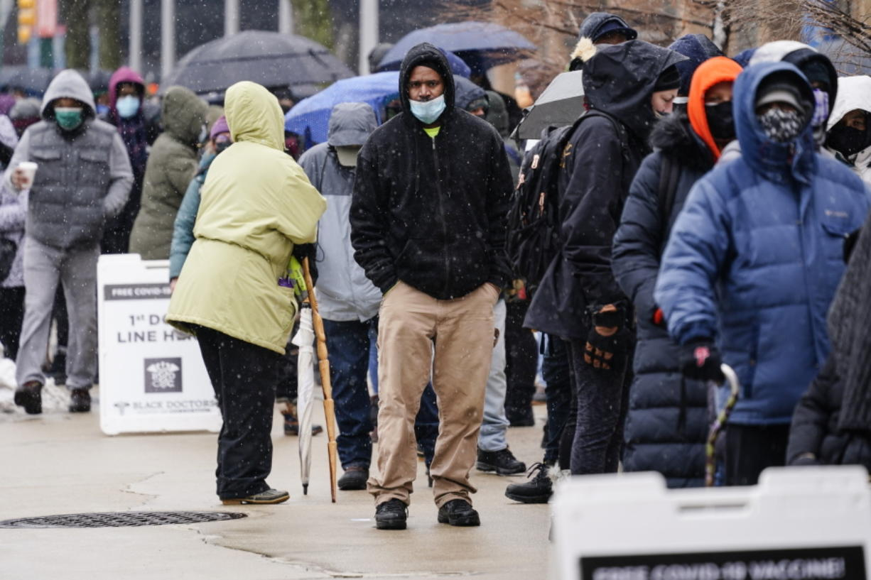 FILE - In this Feb. 19, 2021, file photo, people wait in line at a 24-hour, walk-up COVID-19 vaccination clinic hosted by the Black Doctors COVID-19 Consortium at Temple University's Liacouras Center in Philadelphia. States are scrambling to catch up on coronavirus vaccinations after bad weather last week led to clinic closures and shipment backlogs.