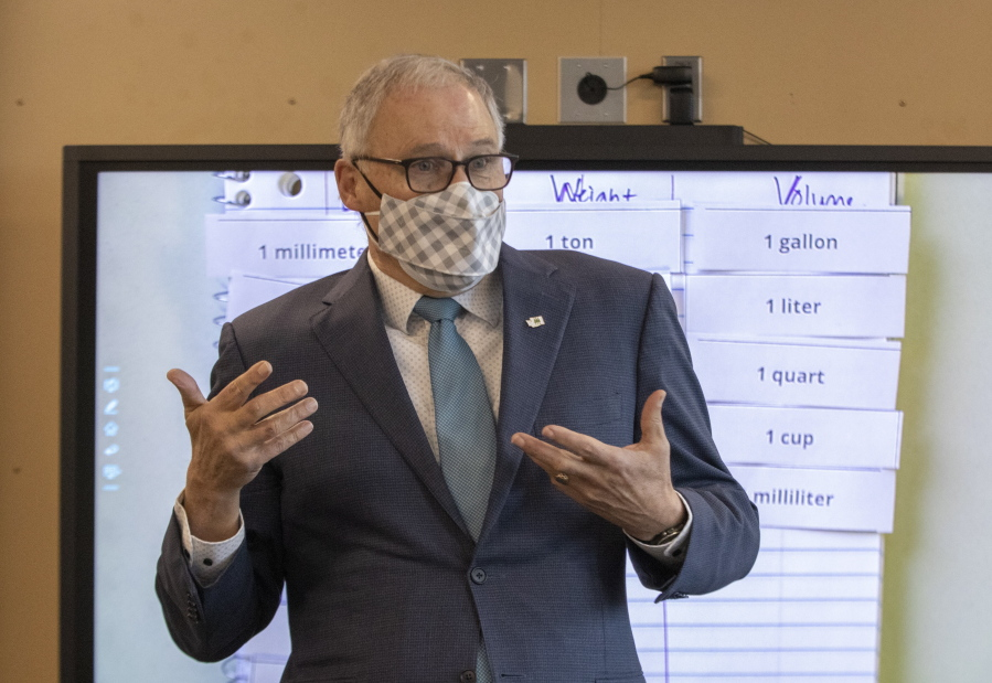 Washington Gov. Jay Inslee speaks with sixth graders in teacher Michelle Dyer's class during a visit to Firgrove Elementary School in Puyallup, Wash., Thursday, Feb. 18, 2021. Students are back in school and all teachers and students are wearing masks. (Ellen M.