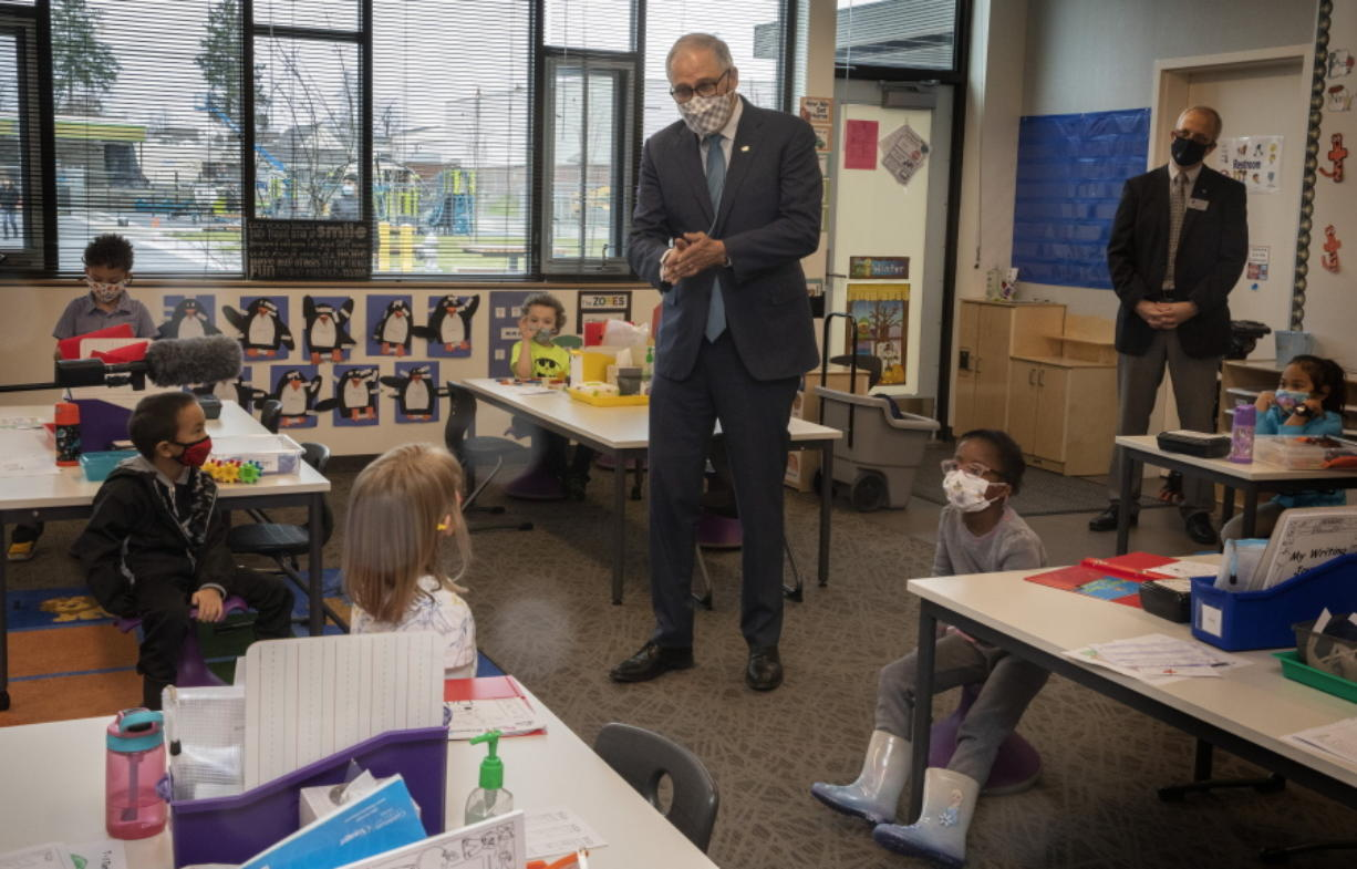 Washington Gov. Jay Inslee speaks with kindergartners in Chelsea Singh's class during a visit to Firgrove Elementary School in Puyallup, Wash., Thursday, Feb. 18, 2021. Students are back in school and all teachers and students are wearing masks. (Ellen M.