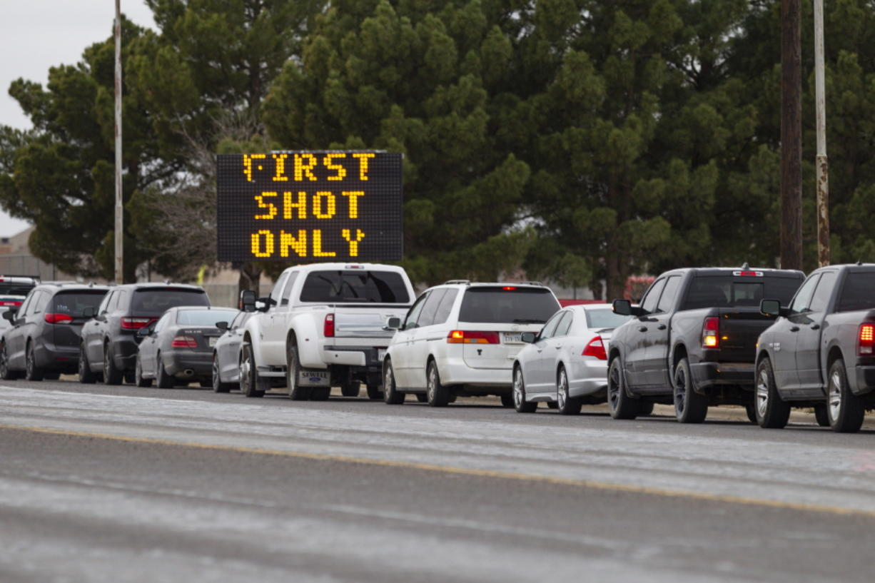 Motorists line up along Yukon Road outside of Ratliff Stadium as they wait to receive the first dose of the Pfizer COVID-19 vaccine at the vaccination clinic held by the City of Odessa and Medical Center Hospital, Thursday, Feb. 25, 2021, in Odessa, Texas.