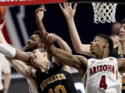 Arizona forward Jordan Brown (21), left, and guard Dalen Terry (4) tangle with Washington guard Erik Stevenson (10) and center Riley Sorn (52) for control of a rebound in the first half of an NCAA college basketball game Saturday, Feb. 27, 2021, in Tucson, Ariz.