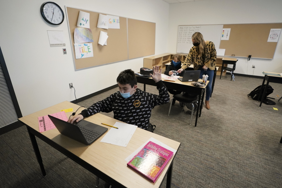 Jonny Velasquez, 9, wears a mask as he raises his hand with a question while working in a fourth-grade classroom, Tuesday, Feb. 2, 2021, at Elk Ridge Elementary School in Buckley, Wash. The school has had some students in classrooms for in-person learning since September of 2020, but other students who attend the school are still learning remotely. Washington Gov. Jay Inslee visited the school Tuesday to observe classrooms and take part in a discussion with teachers and administrators about plans to further open in-person learning in Washington in the future. (AP Photo/Ted S.
