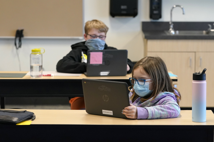 Students wear masks as they work in a fourth-grade classroom, Tuesday, Feb. 2, 2021, at Elk Ridge Elementary School in Buckley, Wash.  (AP Photo/Ted S.