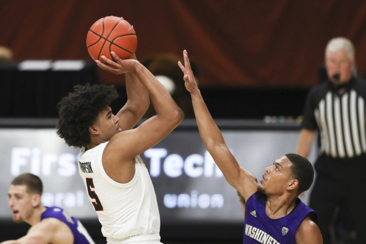 Oregon State's Ethan Thompson (5) shoots over Washington's Quade Green, front right, during the first half of an NCAA college basketball game in Corvallis, Ore., Thursday, Feb. 4, 2021.