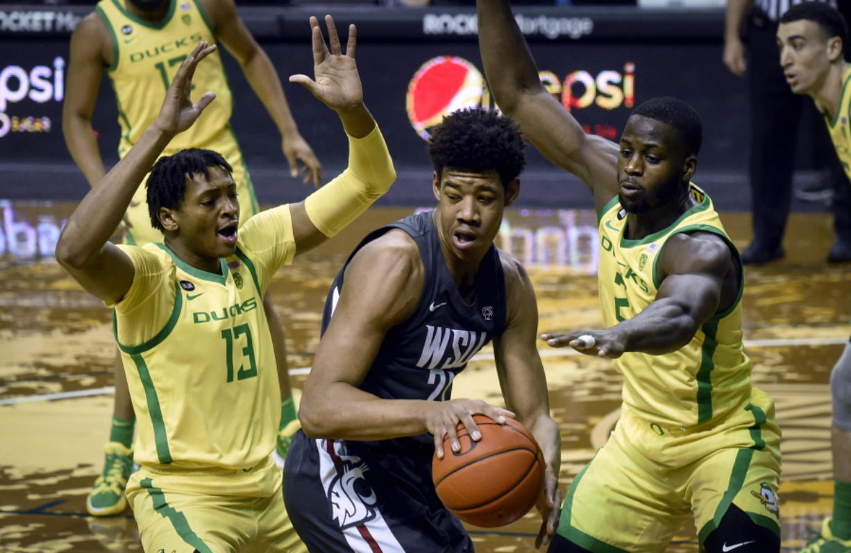 Oregon forwards Chandler Lawson (13) and Eugene Omoruyi (2) pressure Washington State center Dishon Jackson (21) during the first half of an NCAA college basketball game Thursday, Feb. 4, 2021, in Eugene, Ore.