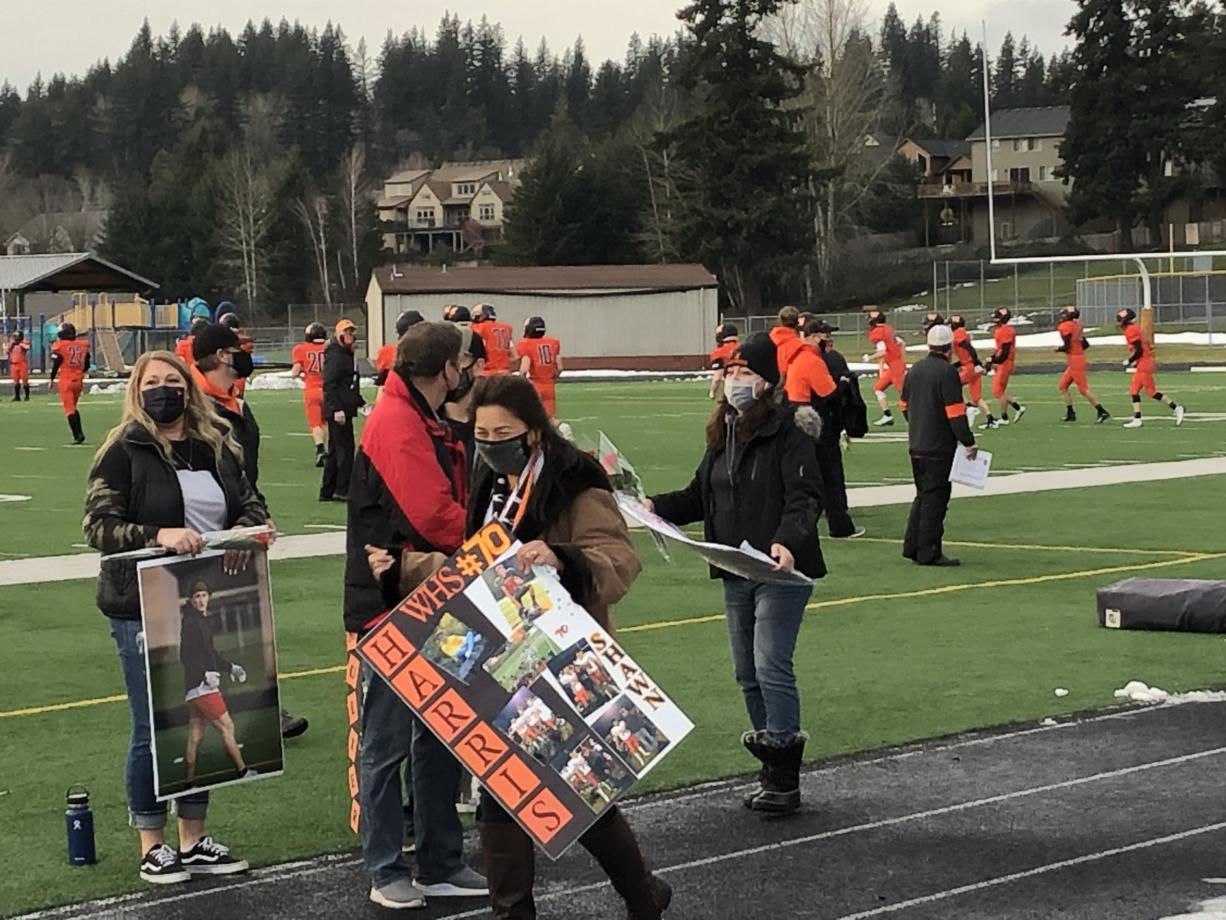Parents of Washougal High School football seniors show special posters before Saturday's game against Mark Morris at Fishback Stadium. With COVID-19 casting uncertainty over the season, Washougal held its Senior Night festivities before its season-opening game Saturday.