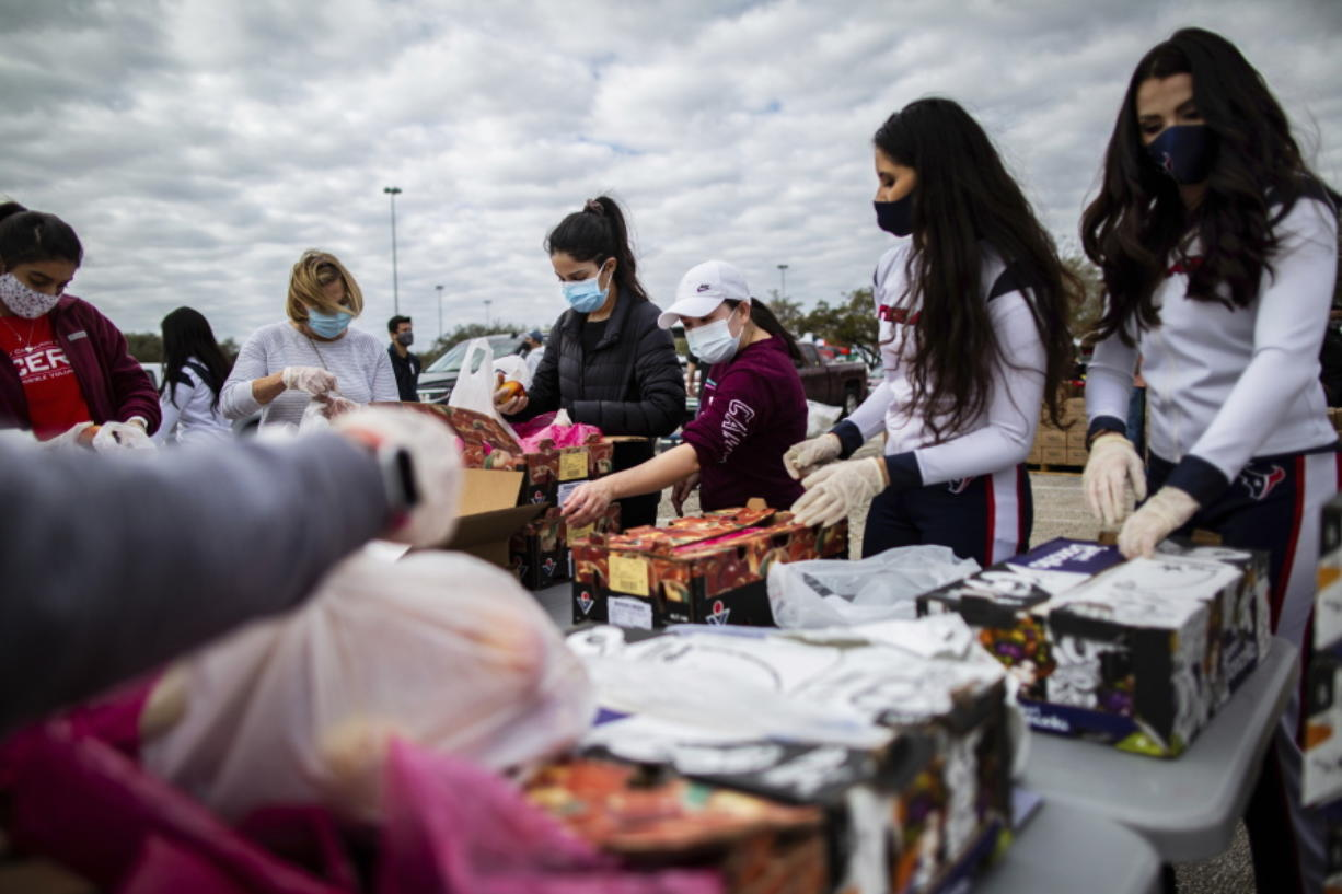 Texans Cheerleaders and other volunteers pack food to distribute to hundreds of people picking up supplies from their cars after frigid temperatures left the Houston area depleted of resources, Sunday, Feb. 21, 2021, in Houston. (Marie D.
