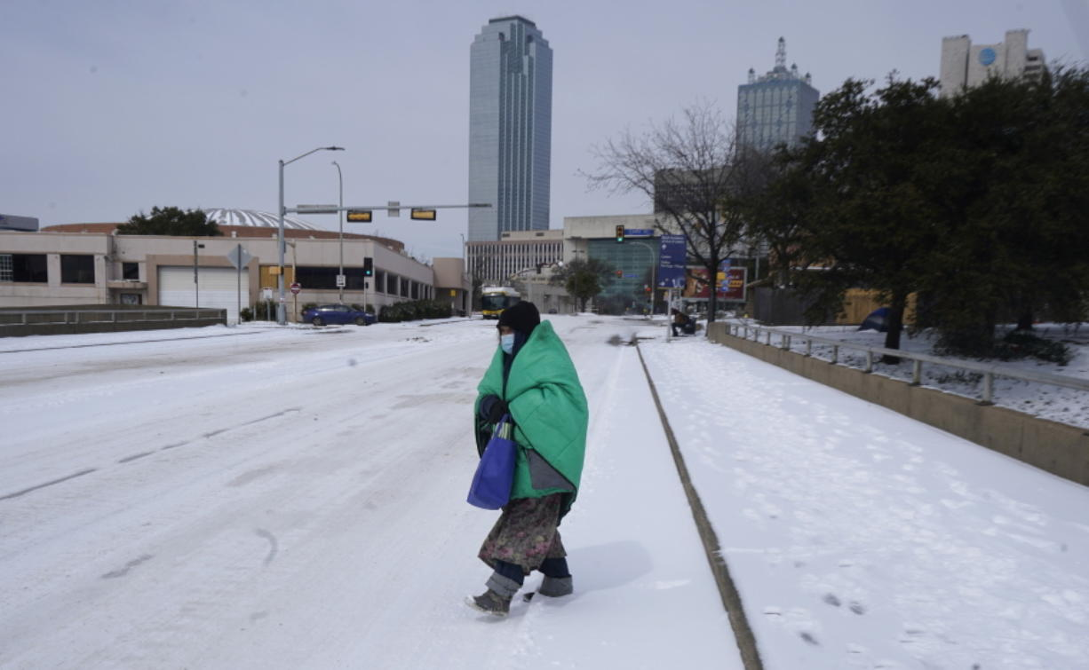FILE - In this Feb. 16, 2021, file photo, a woman wrapped in a blanket crosses the street near downtown Dallas. As temperatures plunged and snow and ice whipped the state, much of Texas' power grid collapsed, followed by its water systems. Tens of millions huddled in frigid homes that slowly grew colder or fled for safety.