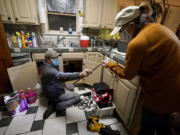 FILE - In this Feb. 20, 2021, file photo, Handyman Roberto Valerio, left, hands homeowner Nora Espinoza the broken pipe after removing it from beneath her kitchen sink in Dallas. The pipe broke during freezing temperatures brought by last week's winter weather.