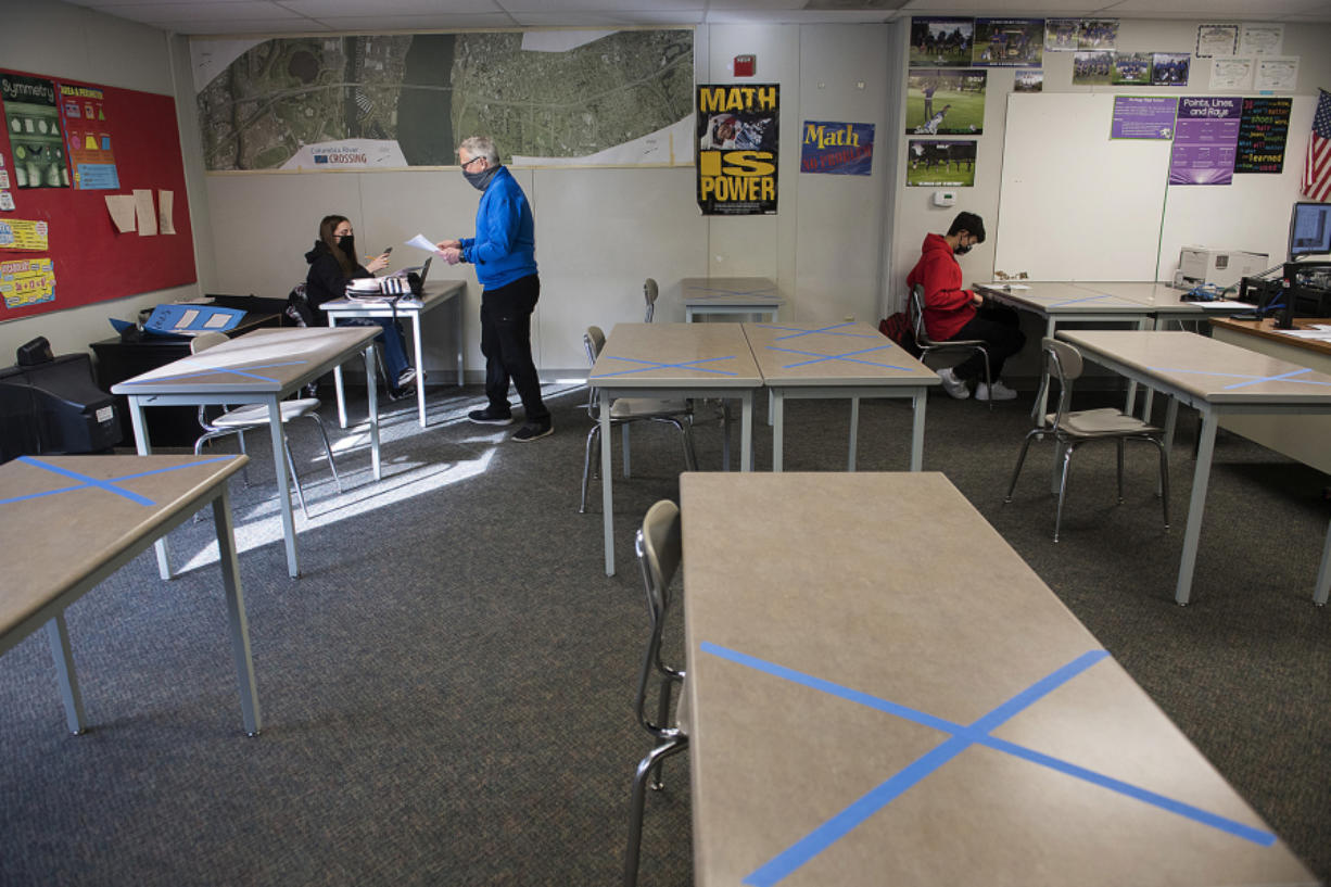Desks at Heritage High School are marked for social distancing as sophomore Mya Beasley, 15, receives a math worksheet from geometry teacher Dwight Patterson on Thursday morning while joined by fellow sophomore Jayden Garcia, 15. Teachers and staff in Evergreen Public Schools welcomed back students in all high school grades for the first time since March 13, 2020, when schools closed due to COVID-19 concerns.