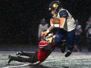 Seton Catholic's Jack Callerme gets hit by Tenino's Randall Marti during Thursday's game in Tenino (Eric Trent/Centralia Chronicle)