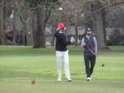 Camas' Eli Huntington, left, hits the ball off the No. 8 tee at Club Green Meadows as Columbia River's Alden Fay watches on Monday.