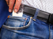 Stock photo of hand pulling a bag of drugs from the front pocket of jeans.