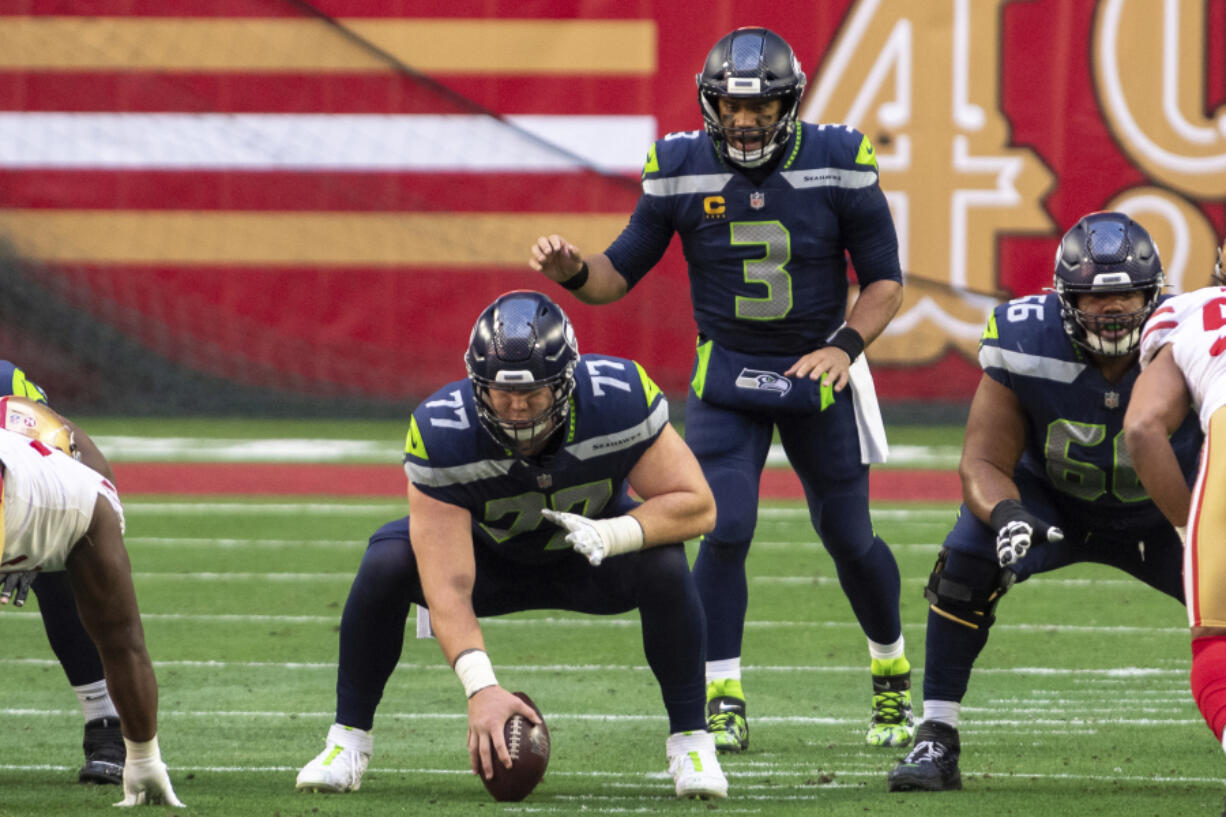 Seattle Seahawks center Ethan Pocic (77) prepares to snap the ball to quarterback Russell Wilson (3) during an NFL football game against the San Francisco 49ers, Sunday, Jan. 3, 2021, in Glendale, Ariz.
