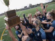 Hockinson senior Kendall McGraw, bottom, lifts the district championship trophy in the air as her team swarms her after the 2A Southwest District Championship on Saturday, March 20, 2021, at District Stadium in Battle Ground. Hockinson won 2-0 to complete a perfect 11-0 season.
