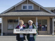 Postmasters Kathy Olson left and Gretchen Goodson holds the Nahcotta Post sign taken down from the building behind them that has been the Post Office for 132 years.  Nahcotta on the Long Beach peninsula population 125 lost its Post Office after USPS didn't renew its lease on the newly purchased property.