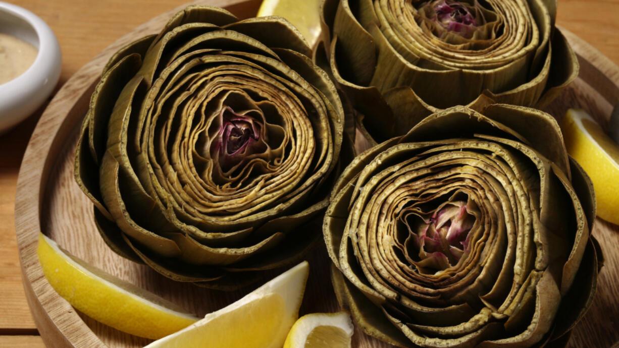 Artichokes steam in a lemon-scented bath until tender. (E.