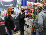Exhibitors at the Central Oregon Sportsmen's Show in Redmond answer questions for a guest about fishing gear they are selling. The show was a first for the region after most such events were shut down by the COVID-19 pandemic, and a trial for the Portland show.