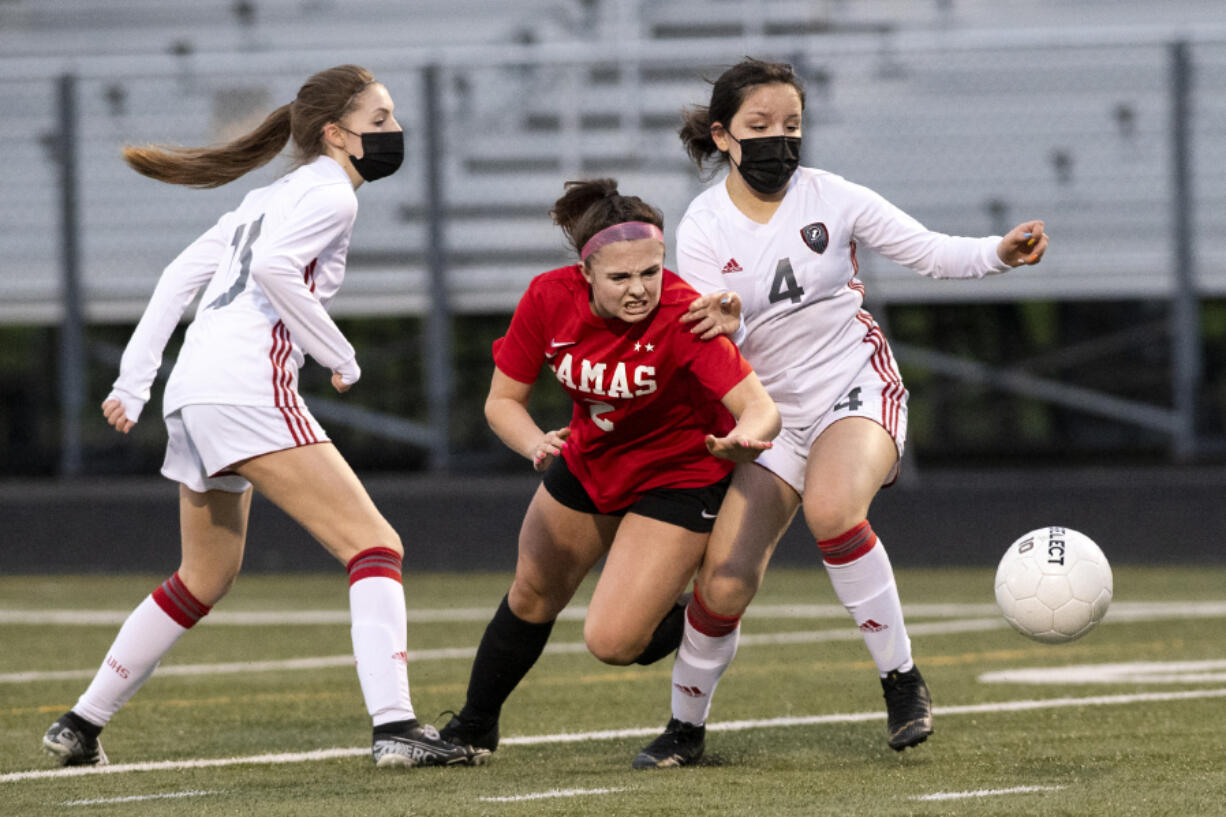 Camas sophomore Bella Burns fights through Union defenders Ashley Elcock, left, and Isabella Barrett in a 4A Greater St. Helens League girls soccer match on Friday, March 26, 2021, at Doc Harris Stadium. Camas won 2-0 to improve to 10-0 on the season.