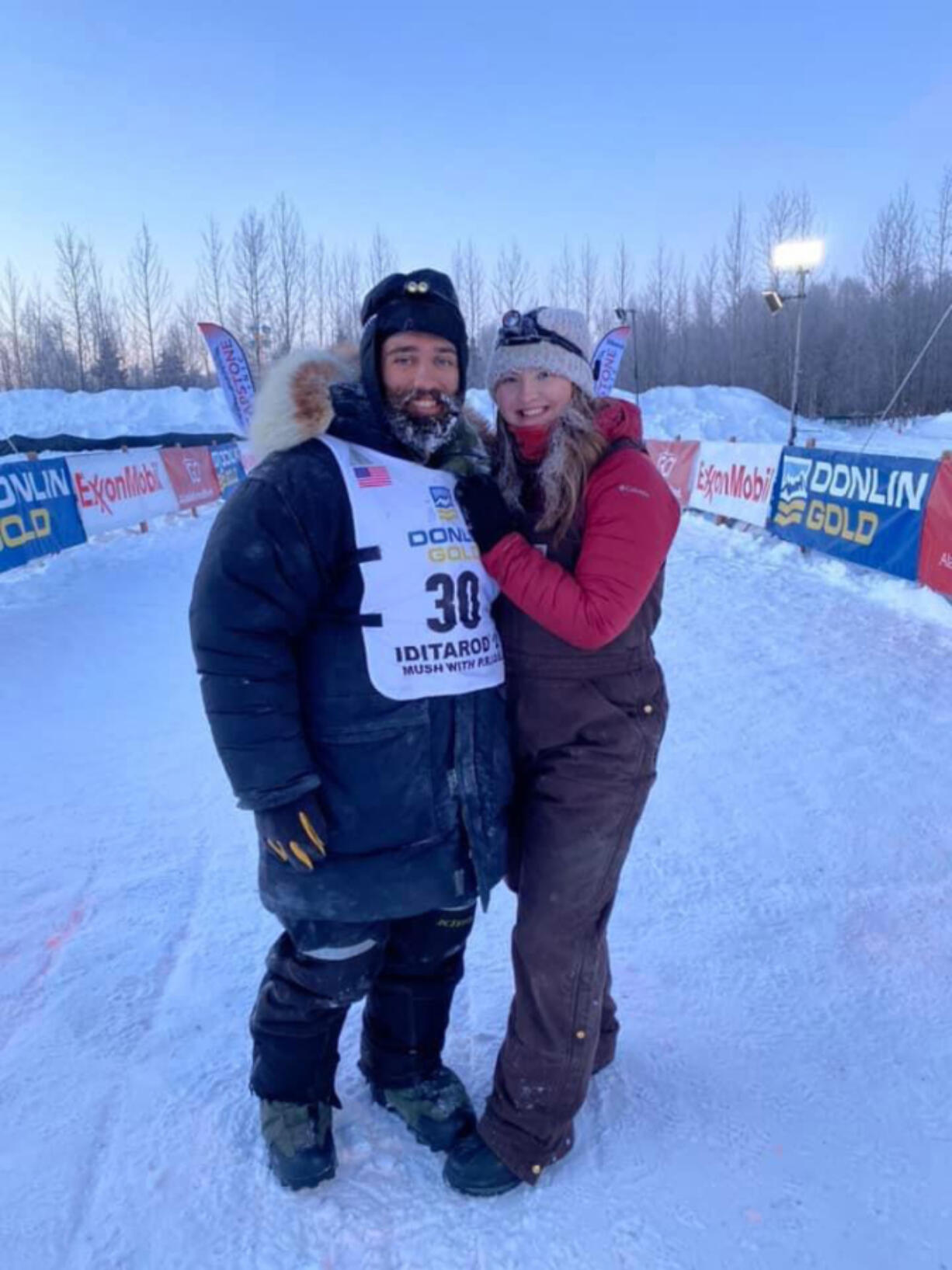 Josh McNeal poses with his wife Jobie after completing the 2021 Iditarod Sled Dog race.