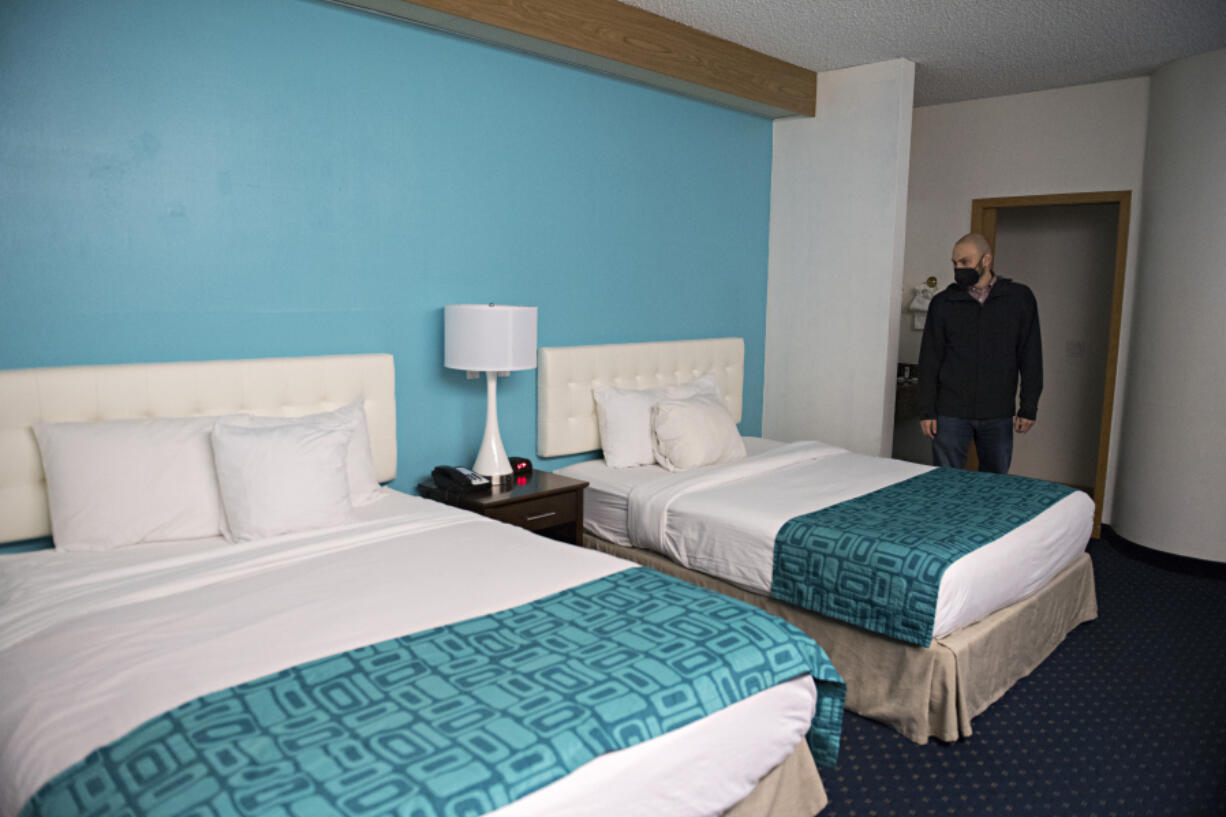 Andy Silver, director of supportive services at the Vancouver Housing Authority, looks over one of the 63 rooms that will be available for homeless residents at the former Howard Johnson hotel during a tour in February.