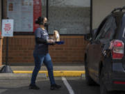 Service team member Selena, who declined to give her last name, serves a customer using the new curbside pickup app at Burgerville Heritage Plaza on Monday afternoon. The company added a tracking option last week through an app called FlyBuy that allows the restaurant to know exactly when customers pull in.