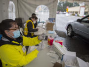 Volunteer pharmacist Serena Donnelly, left, prepares a dose of COVID-19 vaccine while working behind-the-scenes at the new large-scale vaccination site at Tower Mall on Friday morning, March 5, 2021. The vaccinations are by appointment only.