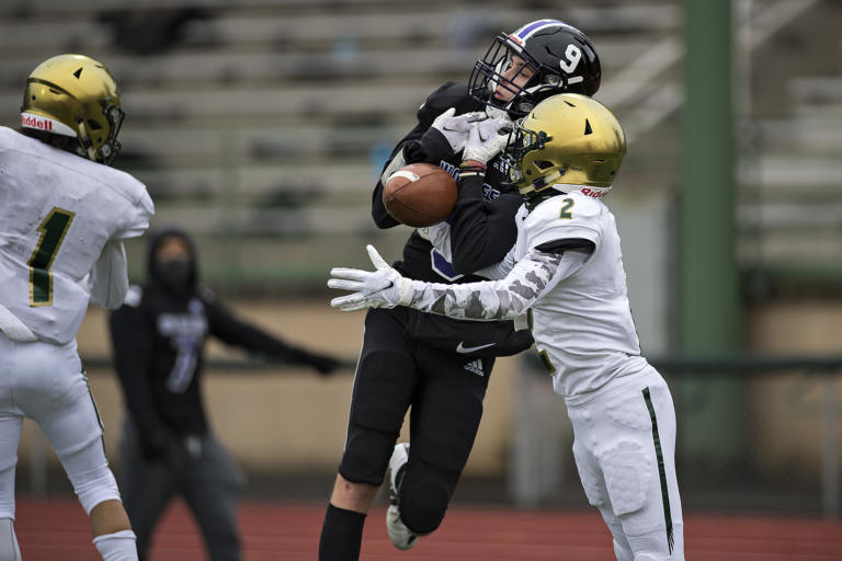 Heritage receiver Alex Anderson (9) is unable to hang onto a pass as Evergreen defender Jonathan Simon (2) breaks up the play in the second quarter as stands at McKenzie Stadium are empty due to COVID-19 concerns on Friday afternoon, March 5, 2021.