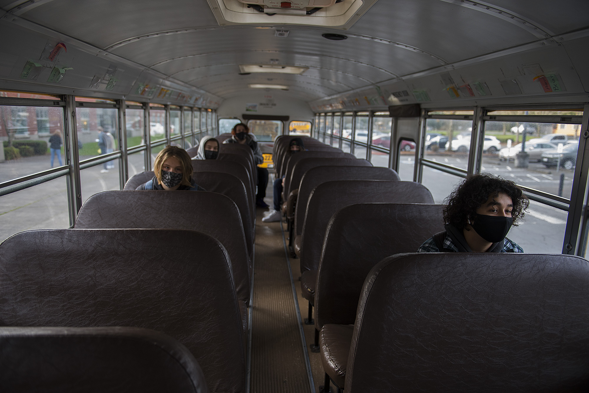 Senior Anthony Lozano, 17, right, joins fellow students on board the school bus as they wait to attend classes in person at Heritage High School on Thursday morning, March 4, 2021. Teachers and staff welcomed back students in all high school grades for the first time since March 13 when schools closed for coronavirus.
