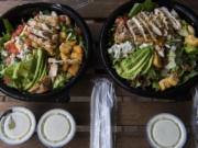 """Avo-Cobb-O salads from Red Robin Gourmet Burgers and Brews, left, and Fresh Set are pictured in their delivery packaging. Fresh Set is one of three """"virtual brands"""" from Red Robin that operates exclusively on delivery apps like DoorDash. At top, the salads are shown listed at Red Robin, left, and Fresh Set on the DoorDash app."""