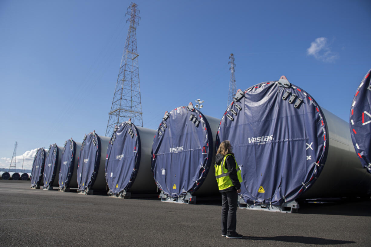 Katie Odem, marketing communications manager for the Port of Vancouver, looks over wind turbine towers that are currently being stored at the port and are waiting to be shipped out by truck. A record-breaking year of wind component imports helped the port during an otherwise challenging 2020 due to the COVID-19 pandemic.