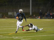 Skyview quarterback Clark Coleman evades a tackle by Union's Jaden Hornsby en route to scoring a touchdown at Kiggins Bowl on Friday night, March 12, 2021.