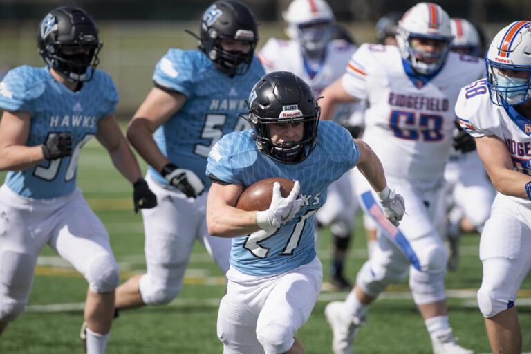 Hockinson's Daniel Thompson scampers away from the rest of the pack as he rumbles to a first-quarter touchdown on Saturday, March 13, 2021, at District Stadium in Battle Ground. Hockinson won 14-7 in the game between the 2A Greater St. Helens League's top two teams.