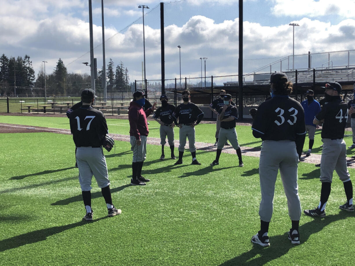 Clark College baseball coach Mark Magdaleno, in red, talks with his team at a practice Wednesday at Ridgefield Outdoor Recreation Complex. Clark's players are playing as the independent club team NW Star after the college canceled spring sports two weeks ago.