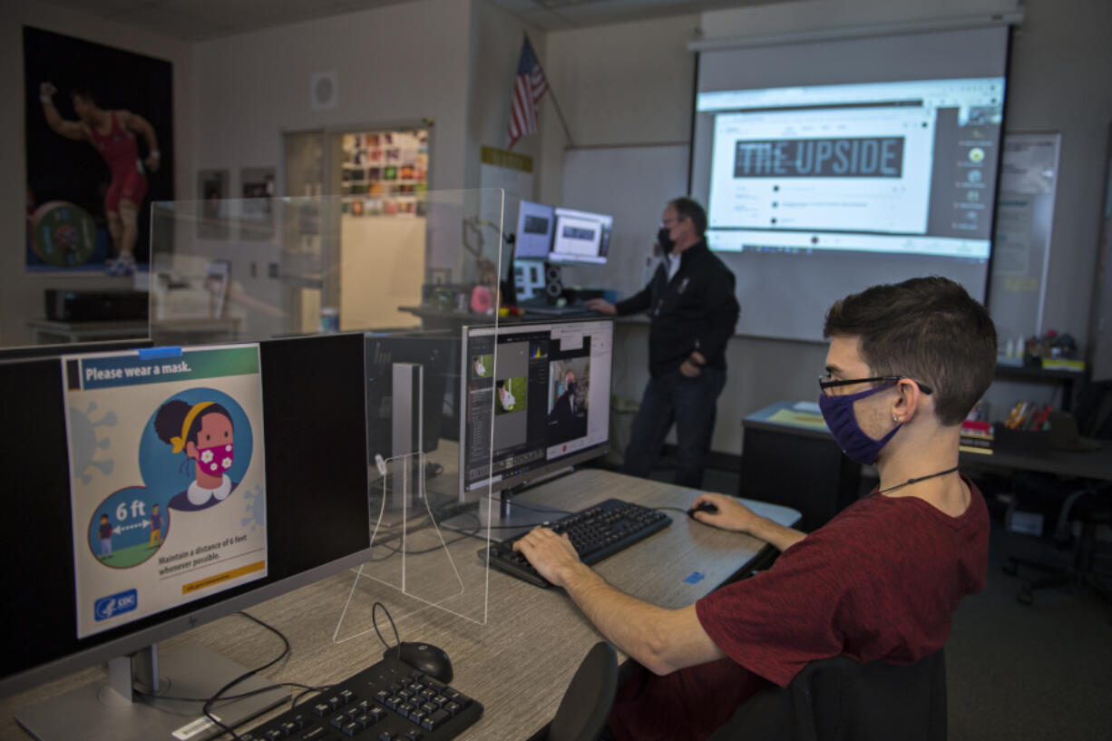 """""""It's not like any other year,"""" said Matthew Trembley, the editor-in-chief of Heritage High School's yearbook. Yearbook staffs around Clark County have faced challenges and complications of different models of instruction, canceled events and activities, absent classmates and limited access as they attempt to pull together a publication reflective of a school year unlike any other. Trembley, right, works on a photograph during adviser Troy Wayrynen's yearbook class last week at Heritage High."""