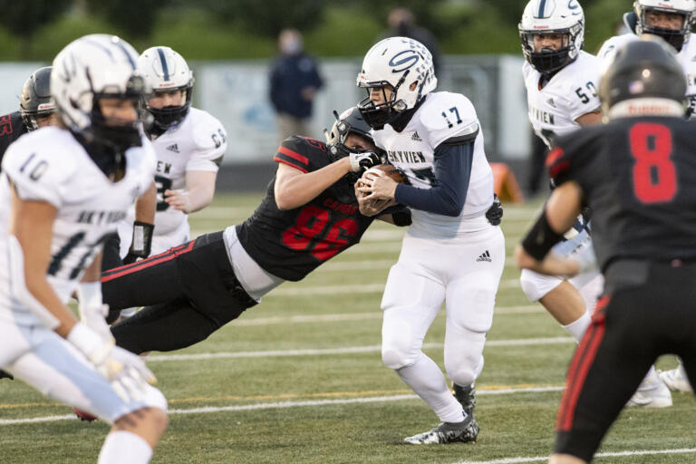 Camas' Holt Williams punches the ball out of Skyview quarterback Clark Coleman's grasp in a 4A Greater St. Helens League football game on Tuesday, March 23, 2021, at Doc Harris Stadium.